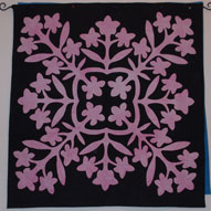 "In Above the Rainbow, the quilt shop owner makes a quilt called ""In the Black at the Pink Plumeria."" After several quilt friends asked if I'd made the quilt described, I decided I should. This is the result, and this quilt was used as the basis for the cover design of St. Rose Goes Hawaiian."